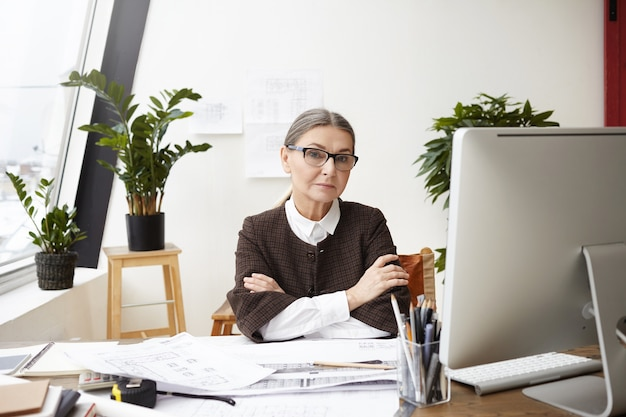 People, occupation, job and age. confident professional senior woman architect in formal clothes and spectacles sitting at her workplace with arms folded, making drawings and using cad program of pc Free Photo