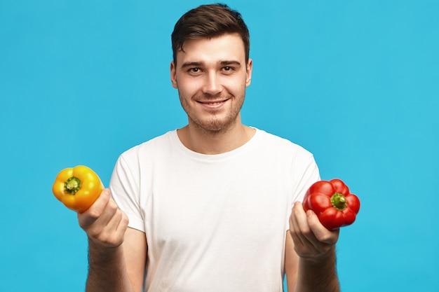 人、有機食品、栄養、菜食主義、健康的なライフスタイルのコンセプト。赤と黄色のピーマンを保持し、サラダを作るつもりの白いtシャツを着ているハンサムなポジティブな若い男性の肖像画 無料写真