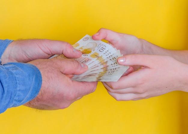 Люди передают деньги друг другу на желтом фоне Premium Фотографии
