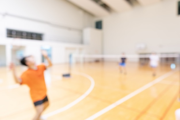 People playing badminton in double teams play at gym court Premium Photo
