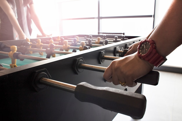 People playing enjoying foosball table soccer game black and yellow players Premium Photo