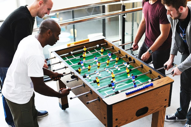 People playing enjoying foosball table soccer game recreation leisure Premium Photo