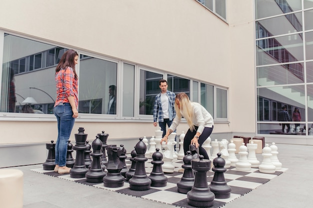 People playing oversized chess outdoors Free Photo