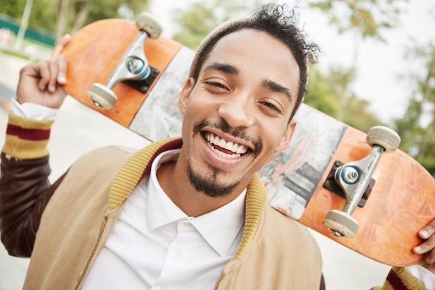 人、心地よい感情、気持ち、アクティブなライフスタイルのコンセプト。ダークスキンの混血の10代の少年がスケートボードを持って、 無料写真