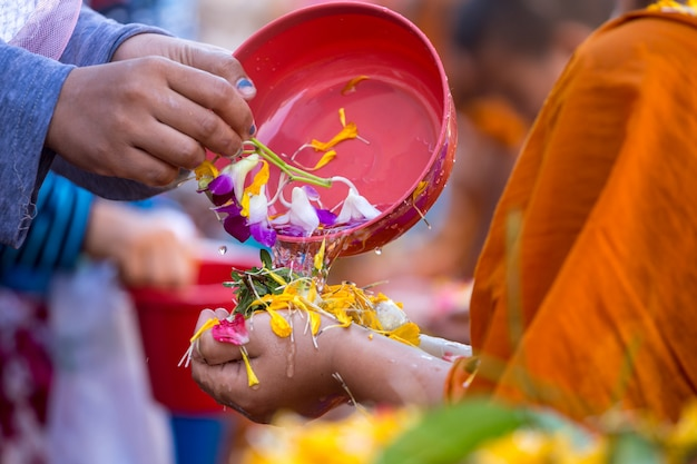 People pouring water to buddhist monks and gives blessing in thailand songkran annual festival in buddhist temple Premium Photo