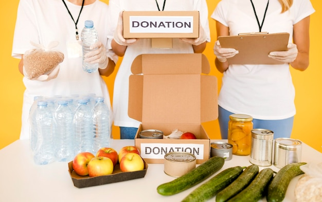 Persone che preparano scatole di donazione con disposizioni per la giornata del cibo Foto Gratuite
