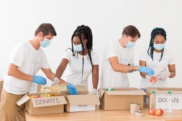 Люди готовят вместе пакеты пожертвований Бесплатные Фотографии