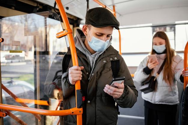 Persone nel trasporto pubblico che indossano la maschera Foto Gratuite