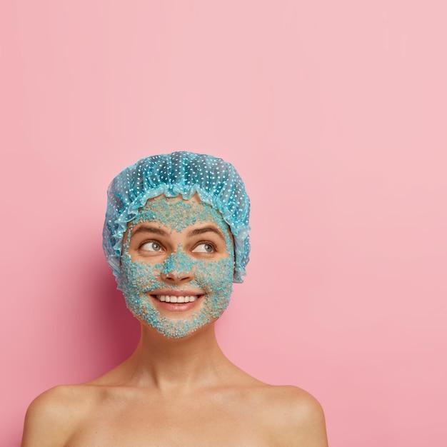 Persone, purezza e concetto di trattamento del viso. la giovane donna sorridente soddisfatta applica lo scrub al sale marino blu, ha il corpo nudo, la pelle pulita e luminosa, indossa il cappuccio della doccia, guarda da parte, ha una procedura di cosmetologia Foto Gratuite