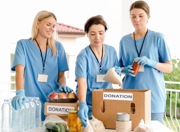 寄付用の箱に食べ物を入れる人 無料写真