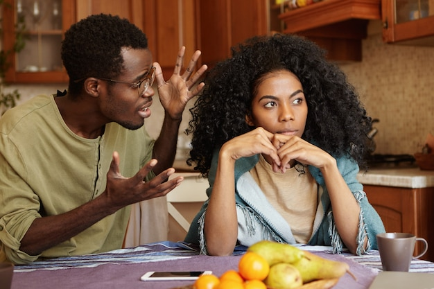 People and relationships concept. african american couple arguing in kitchen: man in glasses gesturing in anger and despair, screaming at his beautiful unhappy girlfriend who is totally ignoring him Free Photo