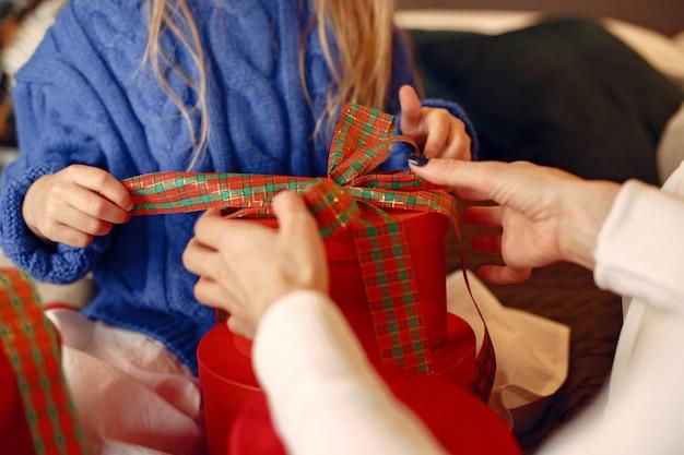 Люди делают ремонт к рождеству. мать играет со своей дочерью. семья отдыхает в праздничном зале. ребенок в синем свитере. Бесплатные Фотографии