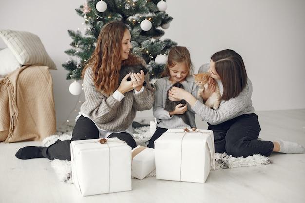 クリスマスの準備をしている人。クリスマスの木のそばに座っている人々。 無料写真
