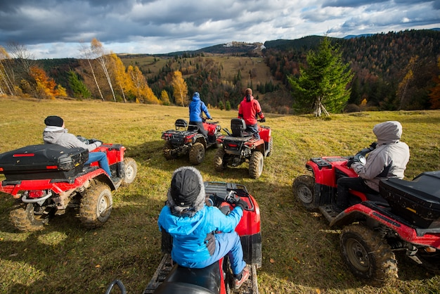 People riding a off-road vehicles on hill Premium Photo