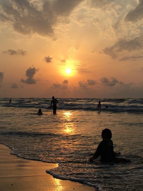People on sea beach at sunset having fun | Premium Photo
