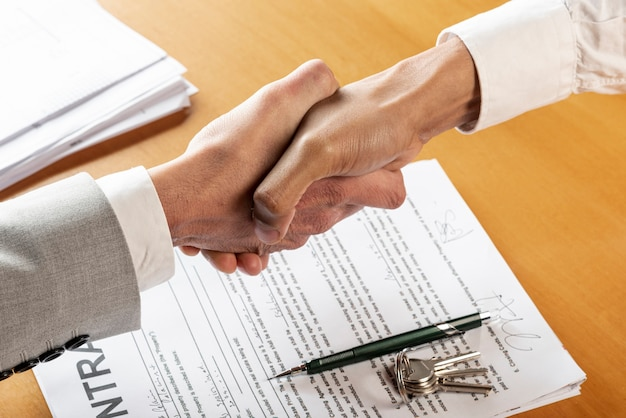 People shaking hands above contract documents Free Photo
