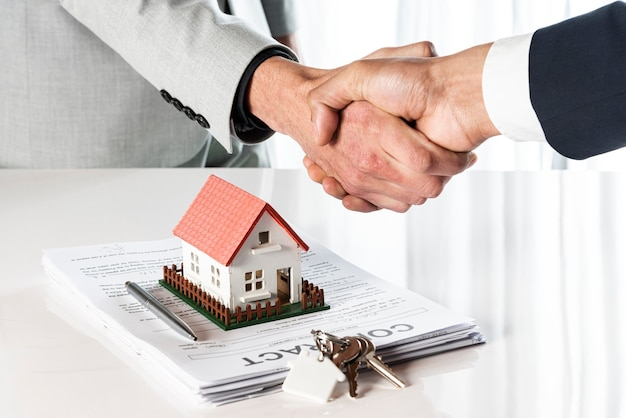 People shaking hands over a toy model house Premium Photo