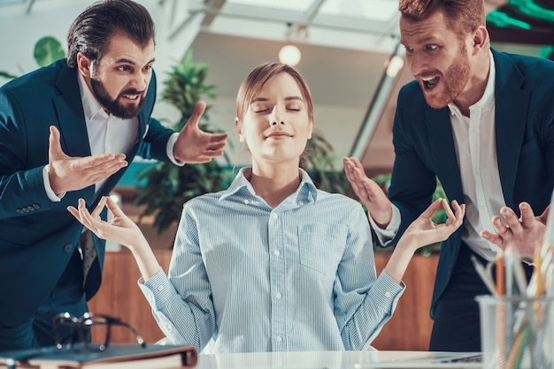 People shout at meditating worker in suit in office. Premium Photo