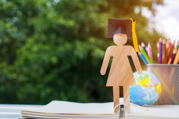 人々は開いた教科書の帽子を祝う卒業と木材を署名する Premium写真