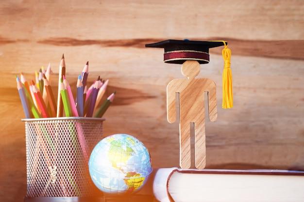 人々は教科書の帽子を祝う卒業と木材を署名する Premium写真