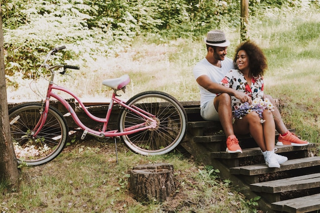 People sit on wooden stairs in park with bike Premium Photo