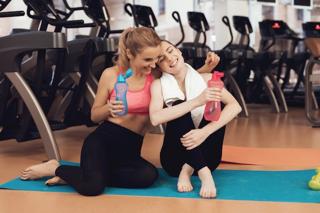 People sitting on mat drinking water at the gym. Premium Photo