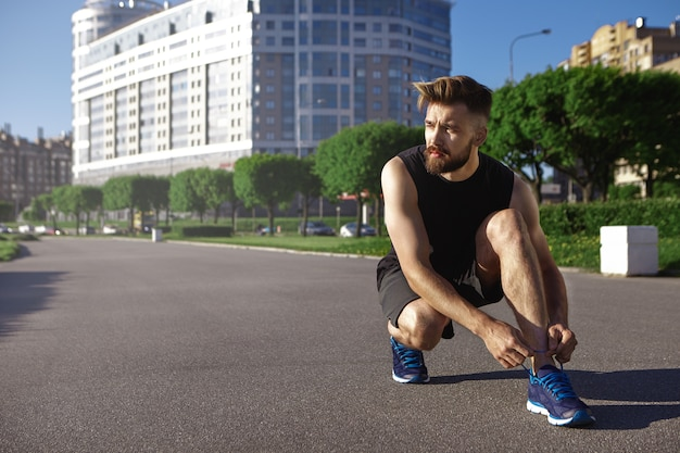 People, sports, active lifestyle and fitness concept. portrait of tired young sportsman with stylish hairdo and thick beard having rest during cardio exercise, sitting on concrete and tying shoe laces Free Photo