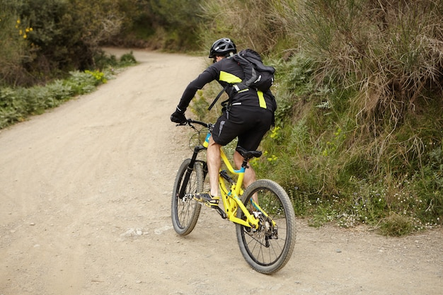 人、スポーツ、極端なリスク、アクティブな健康的なライフスタイルのコンセプト。森の道に沿って高速の黄色のマウンテンバイクに乗ってサイクリング服と防護服を着ている若いヨーロッパの男性サイクリスト 無料写真