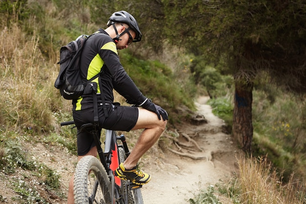 People, sports, extreme and travel concept. young caucasian male rider in cycling clothes having a few minutes break during outdoor training in the morning, exercising on his booster bicycle Free Photo
