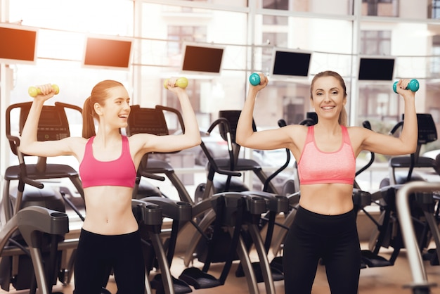 People in sportswear doing exercises with dumbbells at gym. Premium Photo