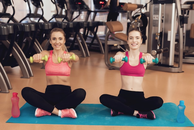 People in sportswear training with dumbbells at gym. Premium Photo