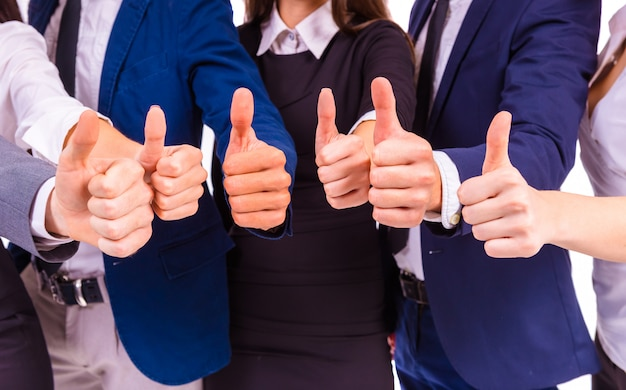 People stand together and keep their thumbs up. Premium Photo