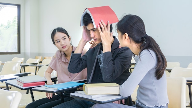 people student read book and hold over head and sit lecture chairs Premium Photo