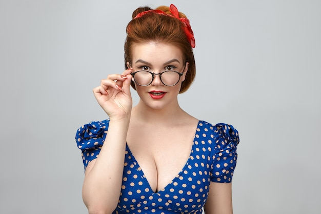 People, style, fashion, optics and eyewear. isolated shot of gorgeous pin up girl model in low cut dress advertising spectacles in studio, holding hand on stylish eyeglasses and smiling at camera Free Photo