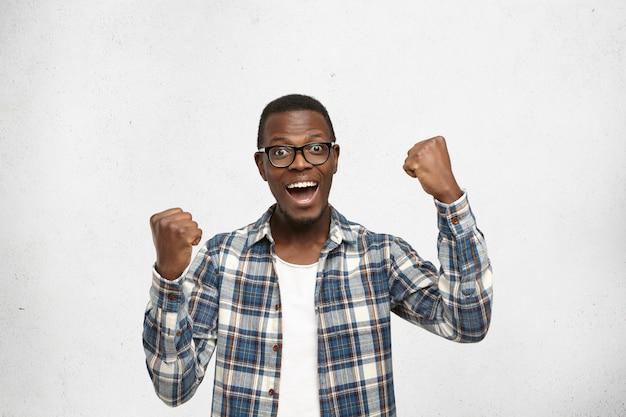 人、成功、達成および勝利の概念。興奮して悲鳴を上げ、拳を握り締めて成功した若いアフリカ系アメリカ人の学生 無料写真