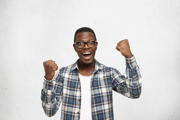 People, success, achievement and victory concept. successful young afro-american student screaming in excitement, clenching fists Free Photo