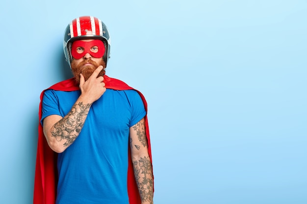 People and super power concept. serious man with red thick beard, wears helmet and red superhero cape Free Photo