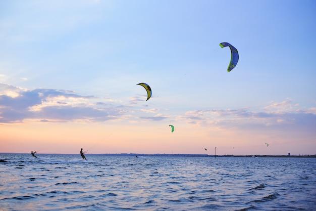 People swim in the sea on a kiteboard or kitesurfing Premium Photo