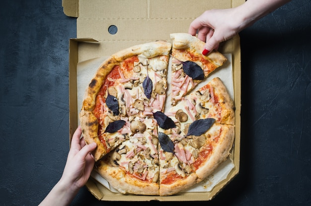 People take a piece of italian pizza in a cardboard box. pizza delivery. Premium Photo