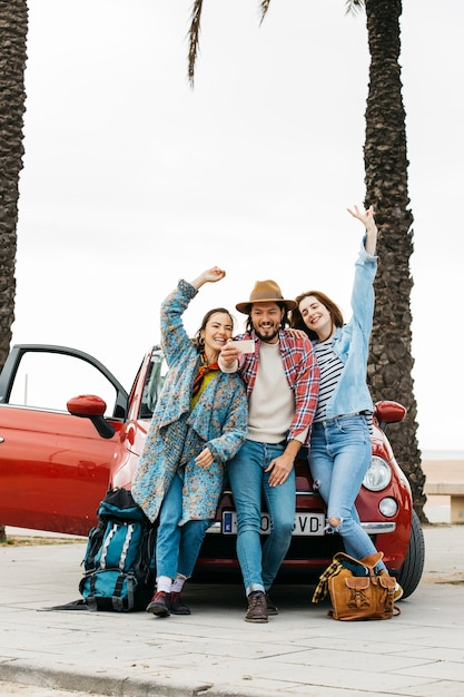 People taking selfie near red car Free Photo