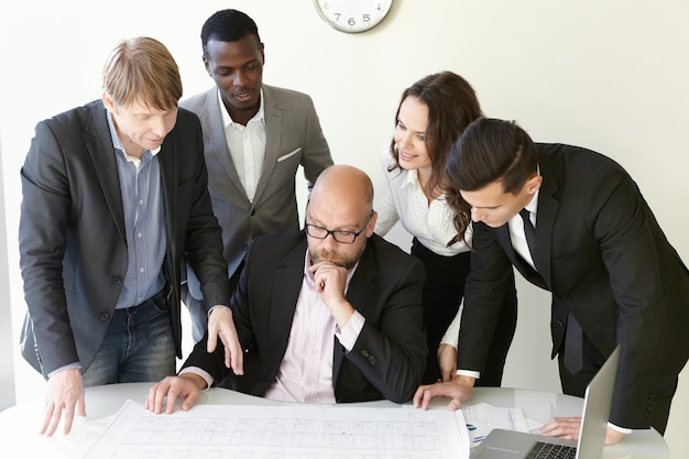 People and teamwork concept. group of engineers working on plan of new building together during brainstorm session. Free Photo