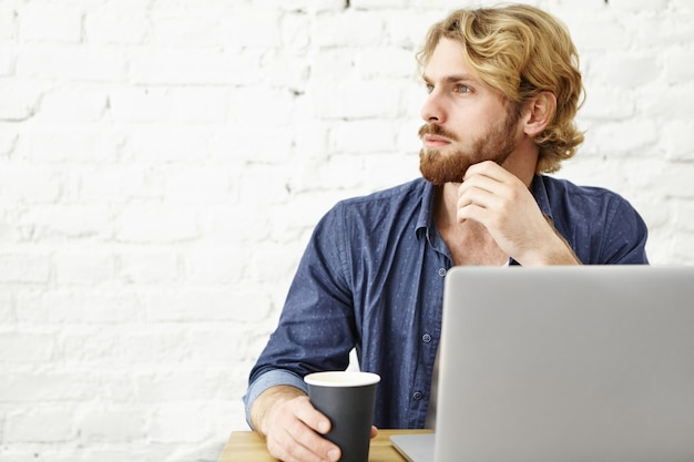 People, technologies and online communication. handsome bearded guy with blonde hair using wifi on laptop during coffee break at cafe, sitting at white brick wall with copy space for your content Free Photo