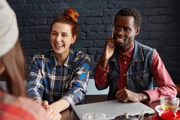 Persone, tecnologia e comunicazione. bella ragazza con i capelli di zenzero, parlando con la sua amica e ridendo, elegante maschio africano in occhiali seduto al tavolo accanto a lei Foto Gratuite