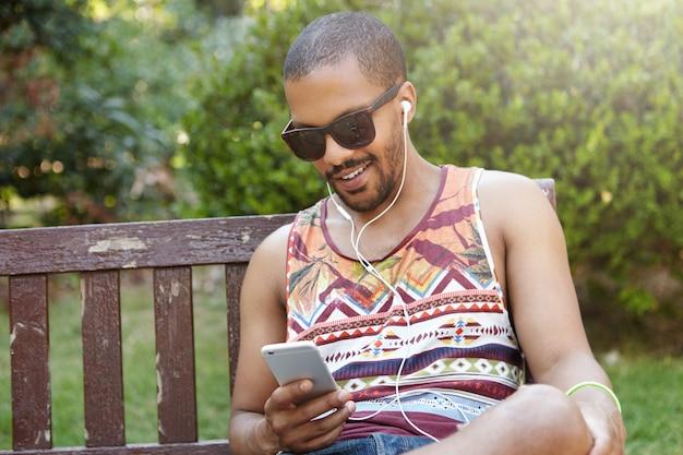 人、テクノロジー、レジャー、ライフスタイル-幸せな流行に敏感な学生が屋外でリラックスしながらスマートフォンを使用してインターネットをサーフィンします。一人でリラックスできるベンチに座っているヘッドフォンを着ている若いフリーランサー 無料写真