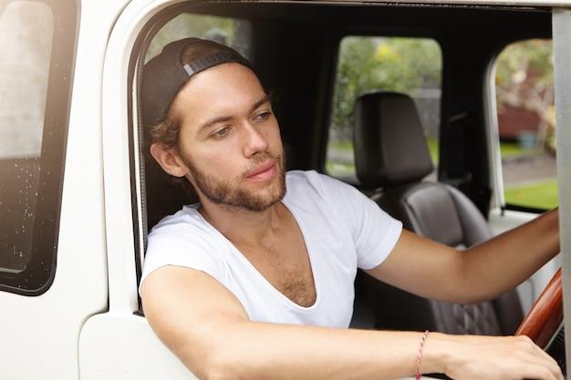 人、交通、レジャー。若いひげを生やした学生彼の白いジープレザーキャビンの内側に座って、道路で彼の前を見てスタイリッシュなスナップバックを着て 無料写真