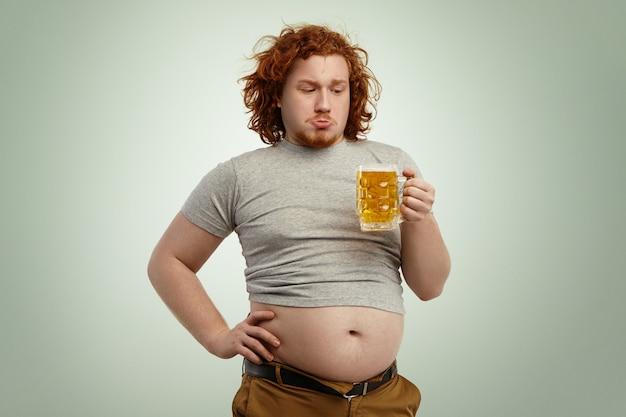 人々、不健康なライフスタイル、肥満、大食い。ビールのガラスを保持している赤い巻き毛の太りすぎの若いヨーロッパ人の太りすぎ 無料写真