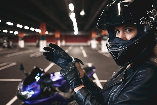 People, urban lifestyle, extreme sports and adrenaline conept. sideways portrait of palyful styligh young caucasian motorcycle rider in fashionable black leather jacket and helmet, adjusting gloves Free Photo