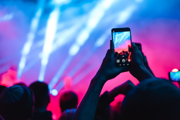 People use smart phones record video at music concert Premium Photo