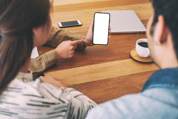 Люди, использующие и смотрящие один и тот же макет мобильного телефона на деревянный стол вместе Premium Фотографии