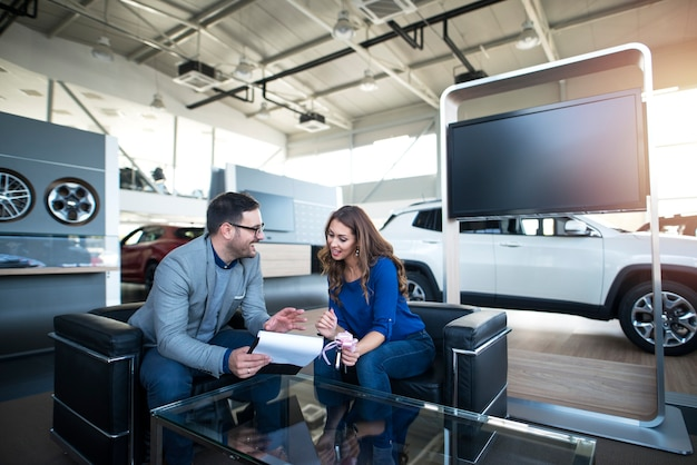 Persone alla concessionaria di veicoli che acquistano auto nuove Foto Gratuite
